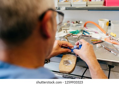 Caucasian man working on a dental prosthesis