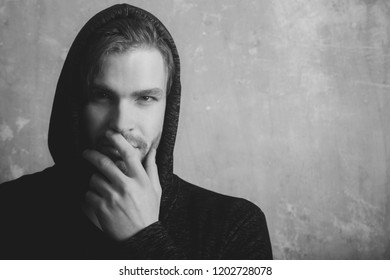 Caucasian man or young model hiding unshaven face with hand wearing fashionable, grey hoodie, hooded sweatshirt with hood on head on beige concrete wall. Secrecy and mystery, copy space
