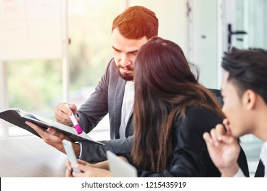 caucasian manager looking at report and discussion with business team at meeting room.