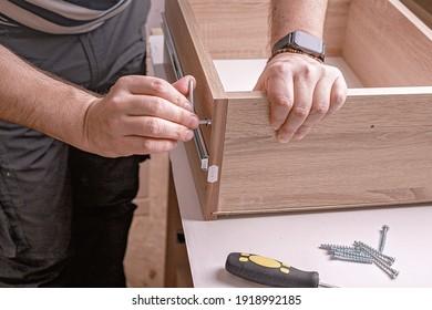 Caucasian mans hands assembling furniture using a screwdriver. Moving in, housework. Close-up.