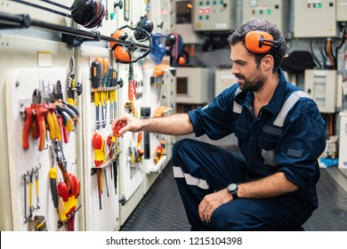 Caucasian marine engineer officer in engine control room ECR. He works in workshop and chooses correct tools and equipment