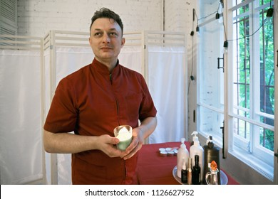 Caucasian masseur holding burning candle standing at the window and looking sideways. Horizontal shot