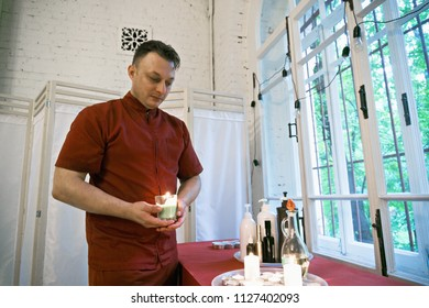 Caucasian masseur holding burning candle standing at the window. Horizontal shot