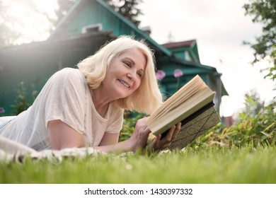 Caucasian mature blonde woman reading a book in the garden. Moment of leisure on summer day. House is on background.