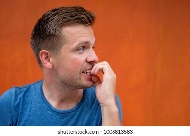 Caucasian mature man on red background gnawing nails. Bad habit when you fell nervous and woryy a lot