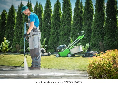 Caucasian Men in his 30s Cleaning Garden Paths and Driveway Using Professional Pressure Washer. Garden Equipment in the Background.