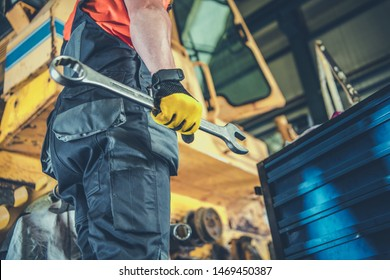 Caucasian Men with Large Iron Wrench Fixing Heavy Machinery. Industrial Job.