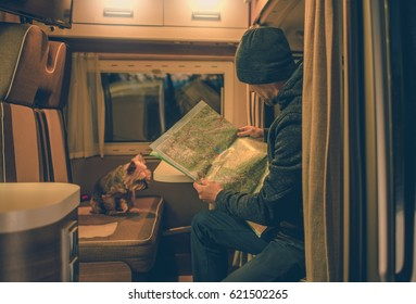 Caucasian Men Planning Trip in His Camper Studying Local Map. His Dog is Seating on Opposite Side of the Motorhome Table. Rving with Pet.