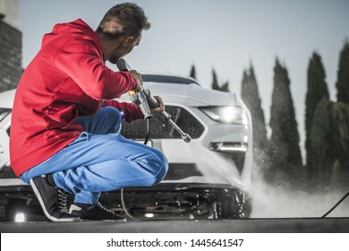 Caucasian Men with Pressure Washing Machine Washing His Modern Car on a Driveway. Taking Care of Vehicle.