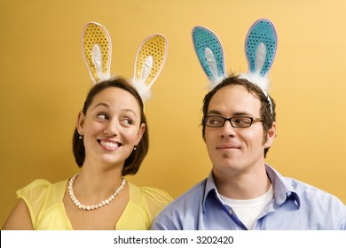 Caucasian mid adult couple wearing rabbit ears and looking at each other.