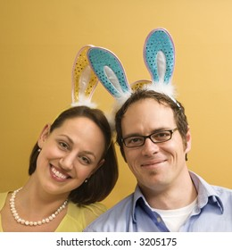 Caucasian mid adult couple wearing rabbit ears and looking at viewer.