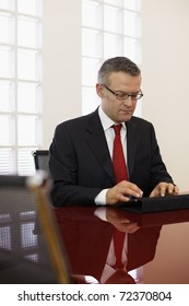 caucasian mid adult male manager typing on tablet pc in meeting room. Vertical shape, side view, copy space