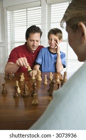 Caucasian mid-adult mother watching mid-adult dad teaching chess to pre-teen son.