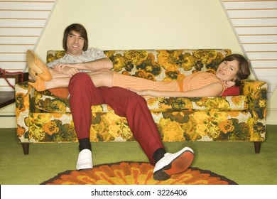 Caucasian mid-adult woman lying on colorful retro sofa with legs draped over Caucasian mid-adult man.