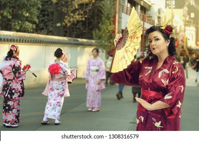 A Caucasian middle aged brunette woman dressed in red kimono with a fan in right-hand stands at other women background dressed in kimono also.