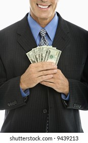 Caucasian middle aged businessman holding fist full of cash.