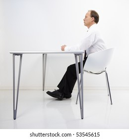 Caucasian middle aged businessman sitting at desk in office.