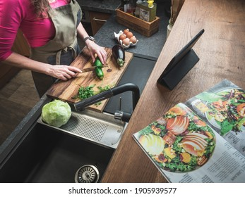 Caucasian middle aged woman in the kitchen follows recipe on digital tablet and food magazine. Healthy food concept.