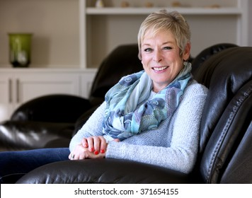caucasian middle aged woman sitting on sofa at home