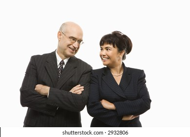 Caucasian middle-aged businessman and Filipino businesswoman standing  with arms crossed against white background smiling at eachother.