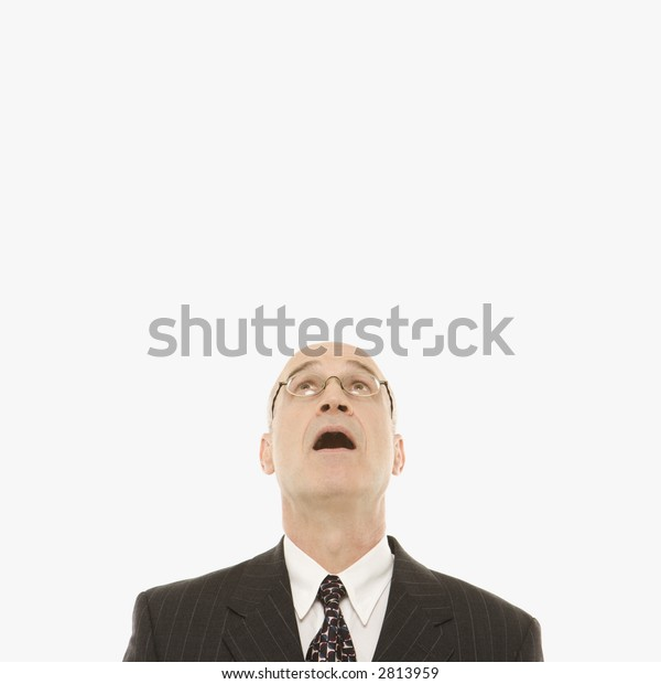 Caucasian middle-aged businessman looking up with mouth open against white background.