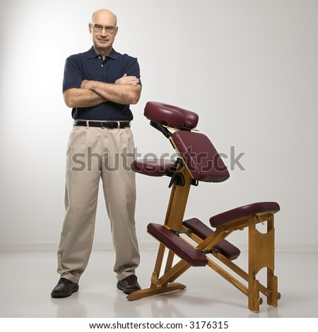 0259301528 Caucasian middle-aged male massage therapist standing with arms crossed  beside massage chair.