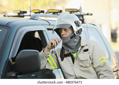 Caucasian middle-aged rescue officer in uniform and helmet talking on radio while standing at car