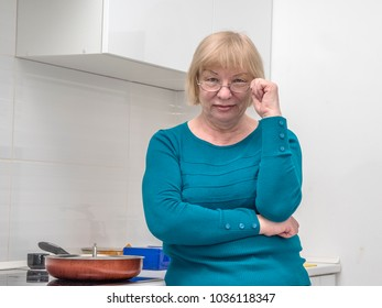 Caucasian middle-aged woman looking at camera over glasses, standing in the kitchen near stove with frying pan