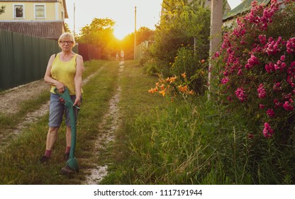 Caucasian middle-aged woman mowing grass on the road in front of a rural house with a trimmer