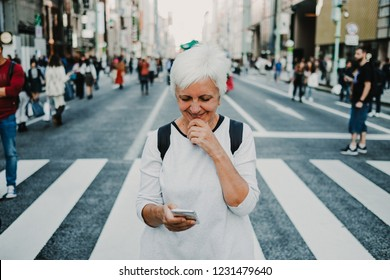 Caucasian middle-aged woman traveling through Japan. Touring the city of Tokyo in one of the neighborhoods with more shops. Using your mobile as a map. Lifestyle.