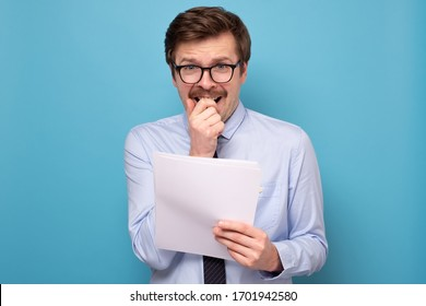 Caucasian millenial man in funny glasses holding his speech at hands reading being afraid of public speech.