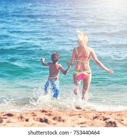 Caucasian mom and son running into the sea water. Back view.
