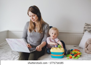 Caucasian mother with baby working online from home on Internet. Workplace of freelancer woman with kid. Coronavirus self-isolation social distance on quarantine. Stay home single mom. A new normal.