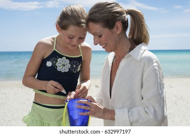 Caucasian mother and daughter looking in bucket on beach