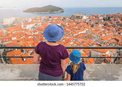 Caucasian Mother and daughter tourists wearnig blue hats standing on top of Old Town Walls in Dubrovnik admiring the view of the historical city below, Croatia