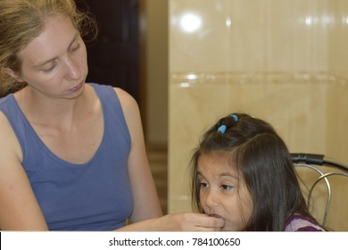 Caucasian mother feeding latin child at home