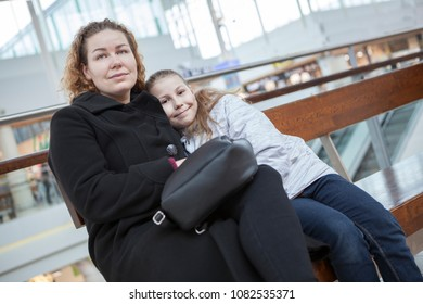 Caucasian mother and her young daughter waiting flight departure in airport lounge