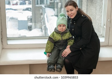 Caucasian mother and little child sitting in warm clothes on window sill inside the hall