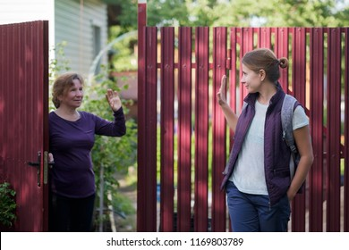Caucasian mother saying goodbye to her daughter as she are leaving. They are standing near red fence of country house