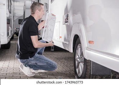 Caucasian Motorhomes RV Technician in His 40s Repair Travel Trailer Refrigerator From Outside. Recreational Vehicles Industry Theme. - Shutterstock ID 1743963773