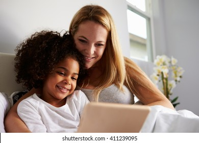 Caucasian mum and black daughter use tablet in bed, close-up