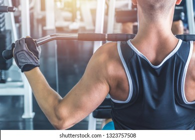 Caucasian muscular man using pull down machine in the gym, weight lifting workout.