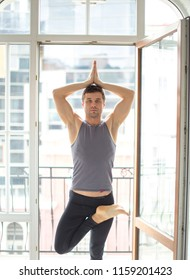 Caucasian muscular yoga male practicing yoga in white well-lit room with big window at home. Vrikshasana, tree pose, view.