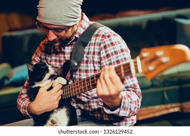 Caucasian musician with cap on head playing with cat while playing bass guitar.