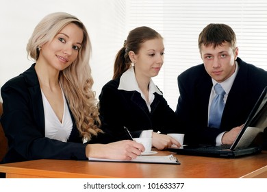 Caucasian nice business company of three men working at a table on a white background