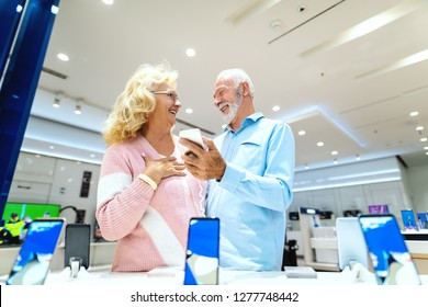 Caucasian old couple discussing about the price for smart phone they want to buy. Tech store interior.