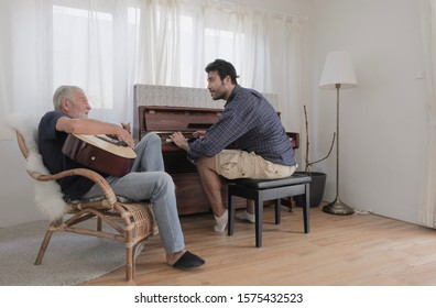 Caucasian old father and his son are happily playing guitar and piano together in vintage living room warmth house on holiday, selective focus.