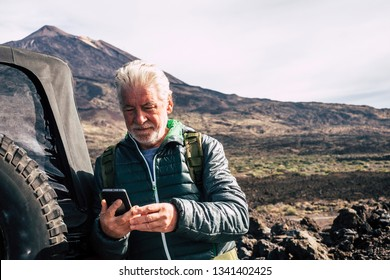 Caucasian old man use modern technology cellular phone at the mountain during trip vacation with off road car at the mountain - planning maps and roads enjoying the nature outdoor for vacation