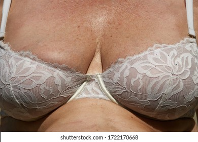 Caucasian older woman in bra with hands on chest.