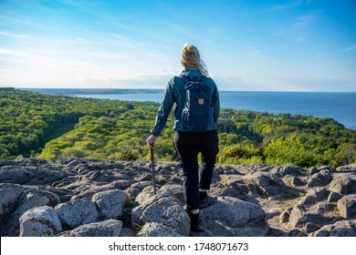 Caucasian Outdoor Active Woman expressing happiness on top of mountain peak at Stenshuvud National Park Overlooking Lush forests with High Biodiversity in Osterlen Skane, South Sweden.